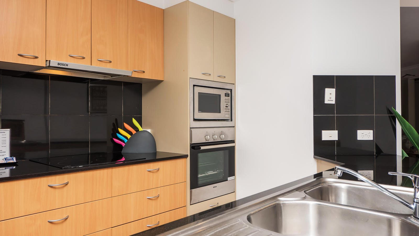Photo showing sink oven and microwave in a well lit clean kitchen