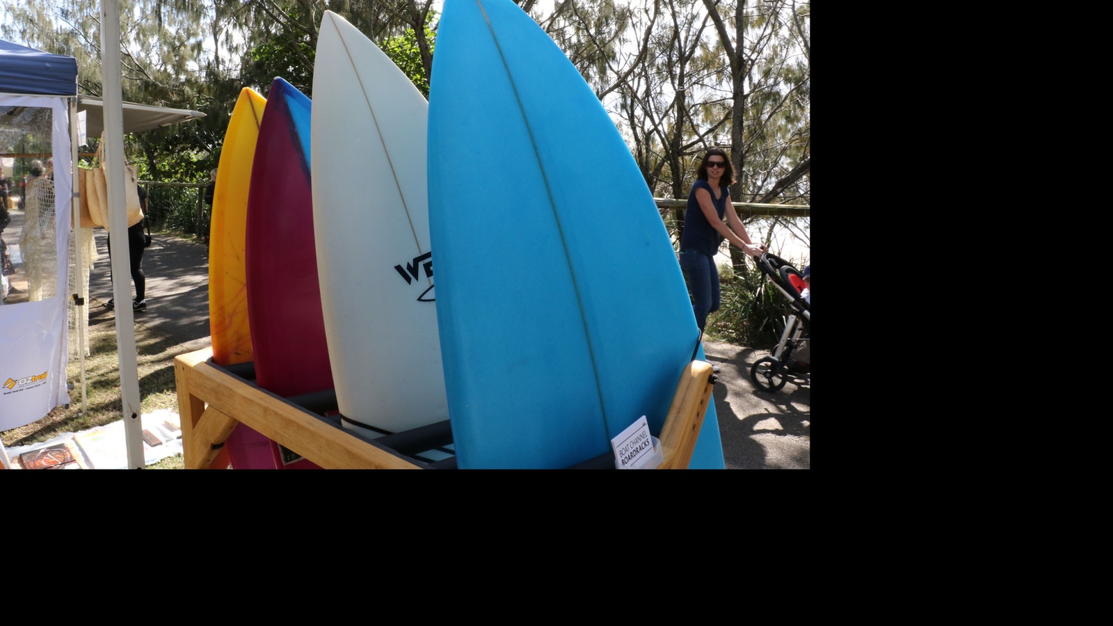 Four colourful surf boards displayed on a rack next to the famous Burleigh  beach break
