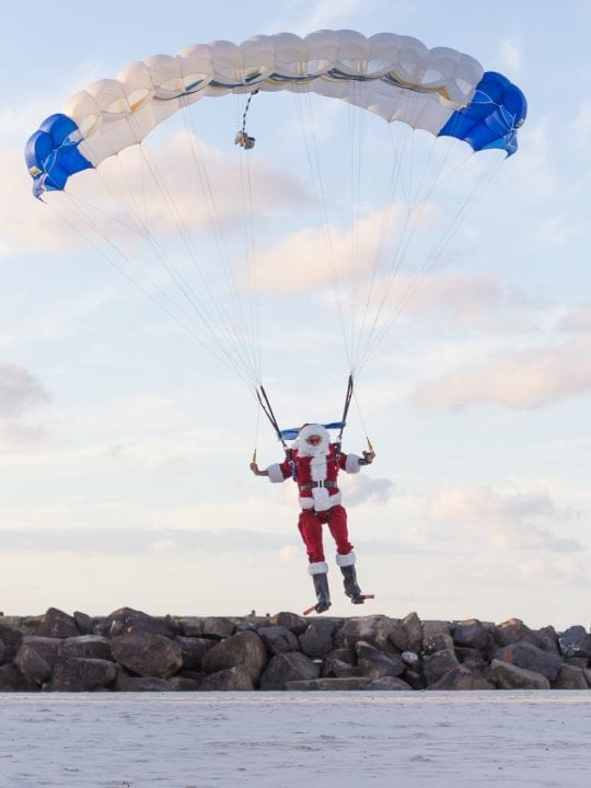 Santa in parachuit landing on Coolangatta beach