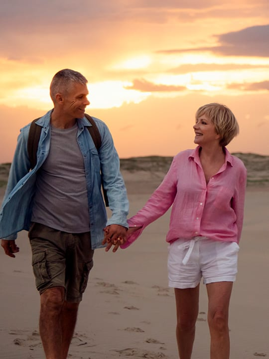 male and female walking on beach